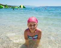 Glückliches lächelndes kleines Mädchen im Meer Stockfotografie