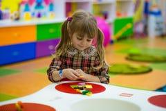 Glückliches lächelndes kleines Mädchen spielt mit buntem Erbauer im Kinderraum Stockfotografie