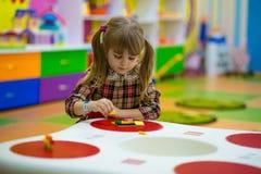 Glückliches lächelndes kleines Mädchen spielt mit buntem Erbauer im Kinderraum Lizenzfreies Stockfoto