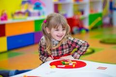 Glückliches lächelndes kleines Mädchen spielt mit buntem Erbauer im Kinderraum Lizenzfreies Stockbild