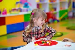 Glückliches lächelndes kleines Mädchen spielt mit buntem Erbauer im Kinderraum Stockfotos
