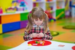 Glückliches lächelndes kleines Mädchen spielt mit buntem Erbauer im Kinderraum Lizenzfreie Stockbilder