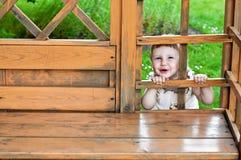 Glückliches lächelndes Mädchen, das heraus zwischen hölzernen Teilen des Gartenhauses schaut Lizenzfreies Stockbild