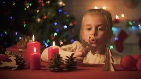 Glückliches lächelndes Mädchen, das nahe funkelndem Weihnachtsbaum, hölzerner Dekor für Feiertag spielt stock video