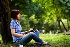 Glückliches lächelndes Mädchen, das online arbeitet Stockbild