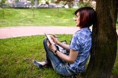 Glückliches lächelndes Mädchen, das online arbeitet Stockbilder