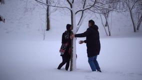 Glückliches lächelndes Mädchen, das von ihrem Freund läuft und hinter Baum sich versteckt Junger Mann fängt seine Freundin, ergre stock footage