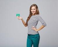 Glückliches lächelndes Mädchen in der Freizeitbekleidung, leere Kreditkarte zeigend stockfotografie