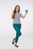 Glückliches lächelndes Mädchen in der Freizeitbekleidung, leere Kreditkarte zeigend stockfoto