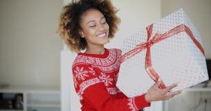Glückliches lächelndes Mädchen mit dem Afro-Haarschnitt, der Geschenk hält stock video