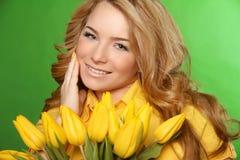 Glückliches lächelndes Mädchen mit den Frühling-blühenden gelben Tulpen lokalisiert Stockfoto
