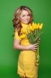 Glückliches lächelndes Mädchen mit den Frühling-blühenden gelben Tulpen lokalisiert Lizenzfreie Stockbilder
