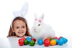 Glückliches lächelndes Mädchen mit ihrem eben gefundenen Ostern-Kaninchen und bunten Eiern auf einer Tabelle stockbild