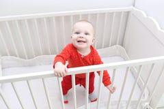 Glückliches lächelndes 6-monatiges Baby, das im weißen Bett steht Lizenzfreie Stockfotografie