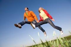 Glückliches lächelndes Paarspringen Lizenzfreie Stockbilder
