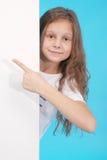 Glückliches lächelndes schönes junges Mädchen, das leeres Schild oder copyspace für Slogan oder Text zeigt Stockbild