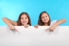 Glückliches lächelndes schönes junges Mädchen zwei, das leeres Schild oder copyspace für Slogan oder Text zeigt Stockbilder