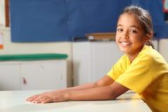 Glückliches lächelndes Schulmädchen 10 im Gelb an ihrem Schreibtisch Lizenzfreies Stockbild