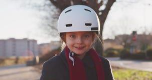 Glückliches lächelndes Schutzhelmreitfahrradporträt des Tochterkindermädchens tragendes am Stadtpark Kindheit, aktiv, Sicherheit stock video