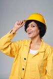 Glückliches lächelndes tragendes Gelb des Frauenerbauers schützen Sturzhelm Stockfotografie