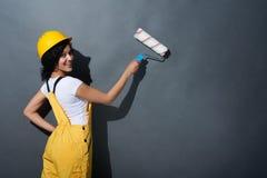 Glückliches lächelndes tragendes Gelb des Frauenerbauers schützen Sturzhelm Stockfotos