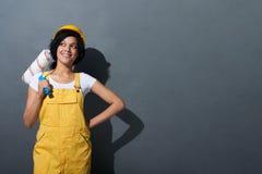 Glückliches lächelndes tragendes Gelb des Frauenerbauers schützen Sturzhelm Lizenzfreies Stockbild