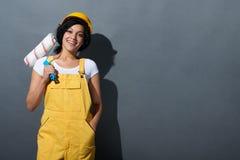 Glückliches lächelndes tragendes Gelb des Frauenerbauers schützen Sturzhelm Stockbild