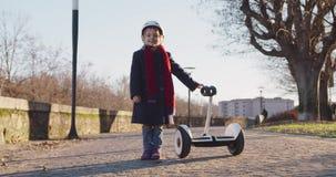 Glückliches lächelndes tragendes Schutzhelmporträt des Tochterkindermädchens mit segway am Stadtpark Kindheit, aktiv, Sicherheit stock video footage