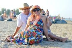 Glückliches lächelndes u. schauendes reifes Paar der Kamera, das an der Küste auf sandigem Strand sitzt Lizenzfreies Stockbild