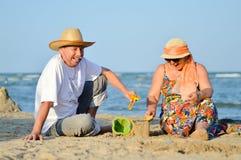 Glückliches lächelndes u. schauendes reifes Paar der Kamera, das an der Küste auf sandigem Strand spielt Stockbild