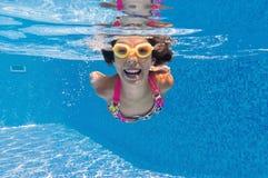 Glückliches lächelndes Unterwasserkind im Swimmingpool lizenzfreies stockfoto