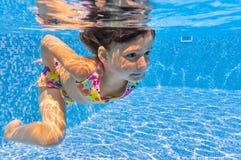 Glückliches lächelndes Unterwasserkind im Swimmingpool stockbilder