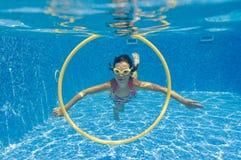 Glückliches lächelndes Unterwasserkind im Swimmingpool stockfoto