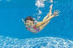 Glückliches lächelndes Unterwasserkind im Swimmingpool stockbild