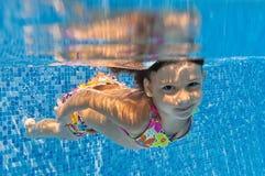 Glückliches lächelndes Unterwasserkind im Swimmingpool stockfotos
