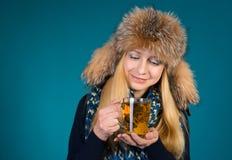 Glückliches lächelndes Winter-Mädchen, das exotischen grünen Tee mit Blumen trinkt Lachende Frau mit Tee-Becher Lizenzfreies Stockbild