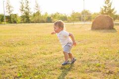Glückliches lachendes Baby, das auf Sommer- oder Herbstfeld spielt stockfotografie