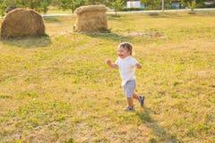 Glückliches lachendes Baby, das auf Sommer- oder Herbstfeld spielt stockfotos