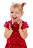 Glückliches lachendes blondes Mädchen mit einem großen roten Apfel Lizenzfreies Stockbild