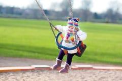 Glückliches lachendes Kleinkindmädchen, das auf Spielplatz schwingt Stockbilder