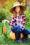 Glückliches Landwirtkindermädchen, das neue Hauptwachstumskarottenernte von eigenem Garten auswählt stockfotografie
