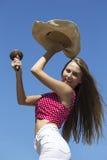 Glückliches langhaariges Mädchentanzen mit maracas und Hut Stockfotos