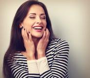 Glückliches laut lachendes Frauenhändchenhalten das Gesicht Stockfoto