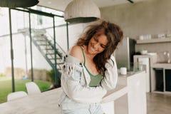 Glückliches Lebensstilporträt des Bezauberns der glücklichen Frau mit tragendem Sommert-shirt des gelockten Haares und Denimjacke lizenzfreie stockbilder