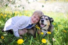 Glückliches Little Boy, das in der Blumen-Wiese sich entspannt und sein Haustier D umarmt stockbild