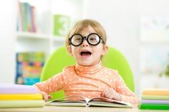 Glückliches lustiges Kindermädchen in den Gläsern ein Buch lesend stockfotografie