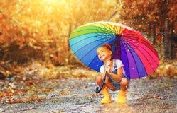 Glückliches lustiges Kindermädchen mit dem Regenschirm, der auf Pfützen im rubb springt stockbild