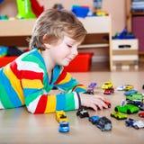 Glückliches lustiges kleines blondes Kind, das mit vielen Spielzeugautos spielt Stockfotografie
