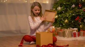 Glückliches Mädchenöffnungs-Weihnachtsgeschenk zu Hause stock footage
