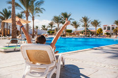 Glückliches Mädchen auf einem Klappstuhl im Sommer, im Urlaub Lizenzfreies Stockfoto